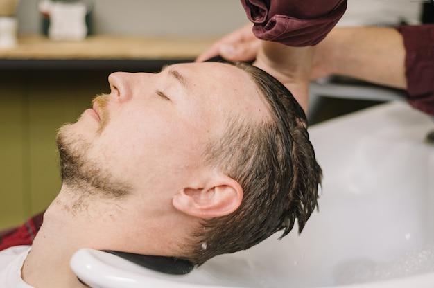 Vista lateral do homem lavando o cabelo na barbearia Foto gratuita
