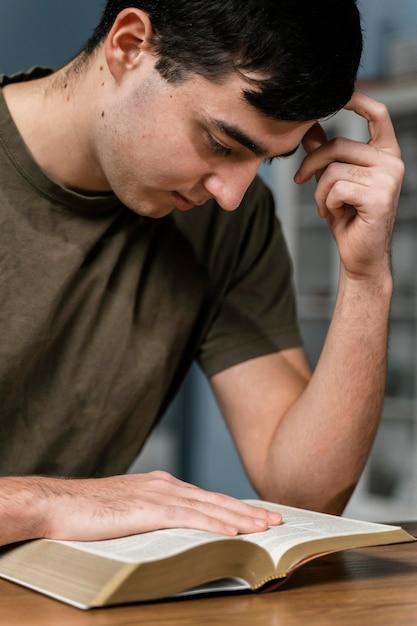 Vista lateral do homem lendo a bíblia Foto gratuita