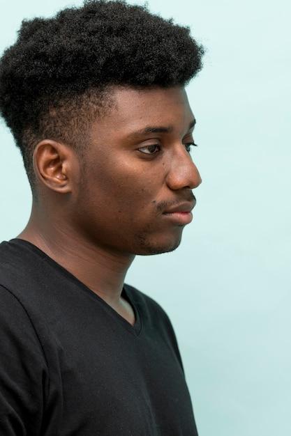 Vista lateral do homem negro triste Foto gratuita