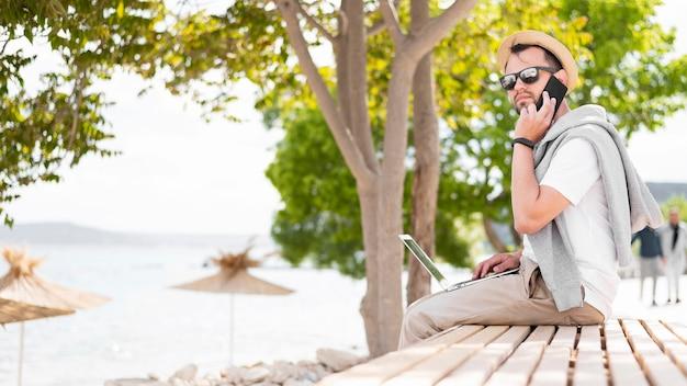 Vista lateral do homem que trabalha na praia com laptop e smartphone Foto gratuita