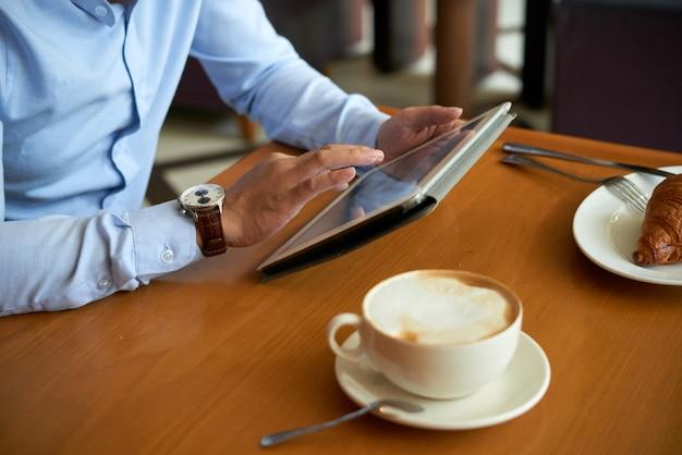 Vista lateral do homem recortado usando aplicativo móvel no tablet pc tomando café com croissant Foto gratuita