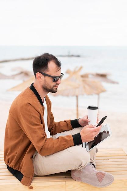 Vista lateral do homem trabalhando na praia enquanto tomando café Foto gratuita
