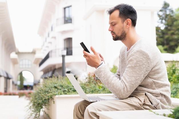 Vista lateral do homem trabalhando no smartphone e laptop ao ar livre Foto gratuita
