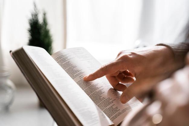 Vista lateral do homem usando o dedo para ler a bíblia Foto gratuita