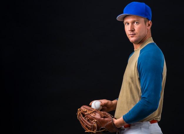 Vista lateral do jogador de beisebol posando com bola e luva Foto gratuita