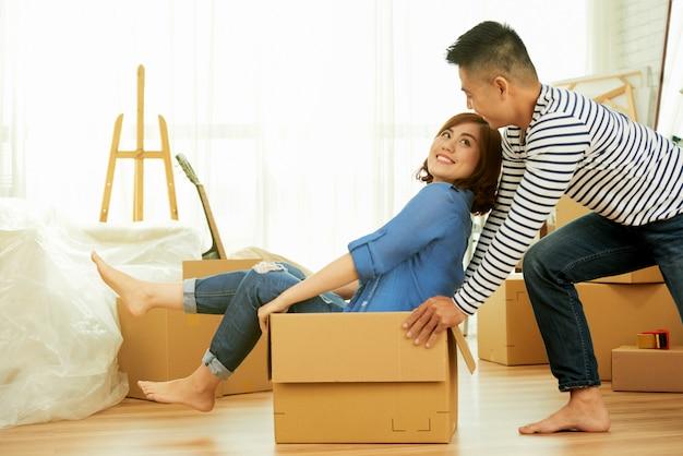 Vista lateral do jovem casal se divertindo com a caixa do pacote em um quarto Foto gratuita