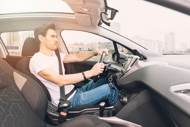 Vista lateral do jovem elegante, dirigindo o carro de luxo Foto gratuita