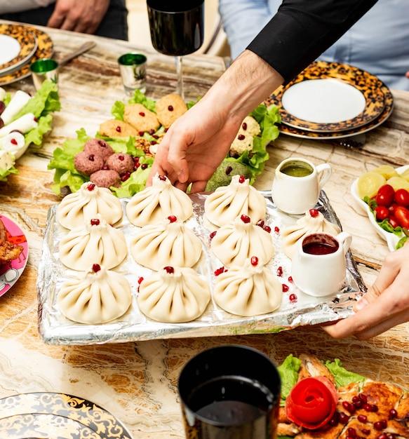 Vista lateral do khinkali georgiano tradicional servido com molhos picantes um molhos na bandeja Foto gratuita