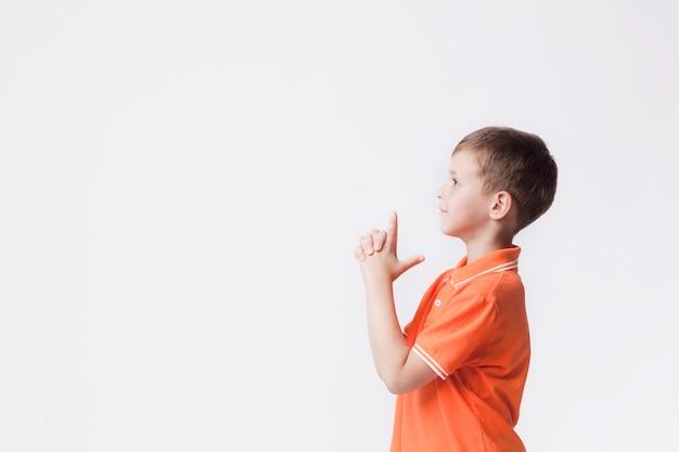 Vista lateral do menino com gesto de arma jogando contra o fundo branco Foto gratuita