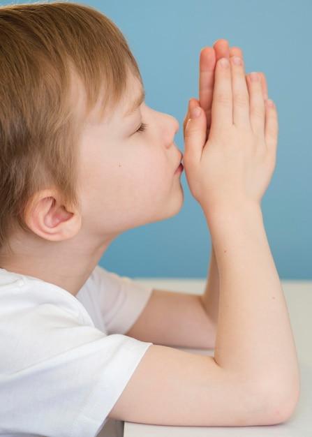 Vista lateral do menino rezando Foto gratuita