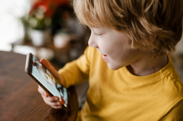 Vista lateral do menino sorridente usando smartphone em casa Foto gratuita