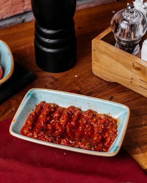 Vista lateral do molho de pimenta quente chamado adjika em um prato sobre uma mesa de madeira Foto gratuita