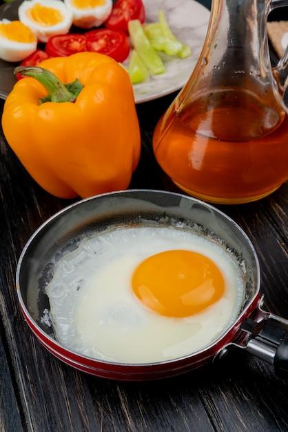 Vista lateral do ovo frito em uma frigideira com vinagre de maçã com uma pimenta laranja em fundo de madeira Foto gratuita