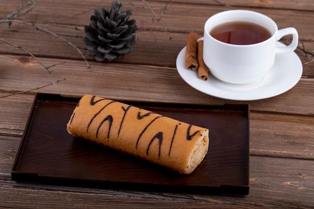 Vista lateral do rocambole com geléia de damasco em uma placa de madeira, servida com uma xícara de chá em fundo rústico Foto gratuita