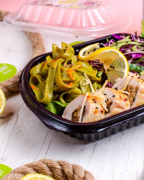 Vista lateral do rolo de frango recheado com alho vegetal e nozes, servido com salada de repolho e fatia de limão na caixa de entrega Foto gratuita