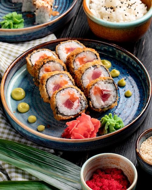 Vista lateral do rolo de sushi com caranguejo e atum em um prato com gengibre e wasabi na superfície de madeira Foto gratuita