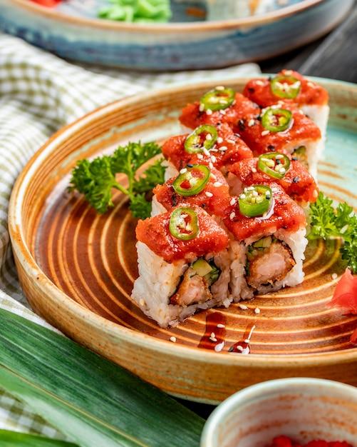 Vista lateral do tempura sushi maki com camarão e abacate em um prato com gengibre e wasabi Foto gratuita