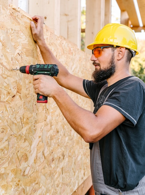 Vista lateral do trabalhador da construção civil perfurando madeira compensada Foto gratuita