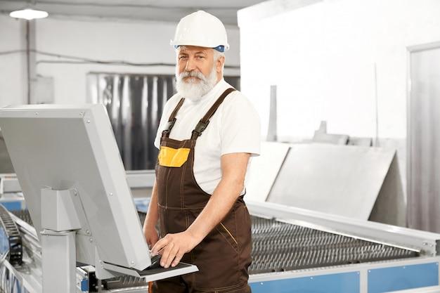 Vista lateral do trabalhador profissional da fábrica de metal Foto gratuita