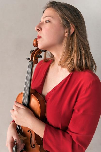 Vista lateral do violinista feminina posando com violino Foto gratuita
