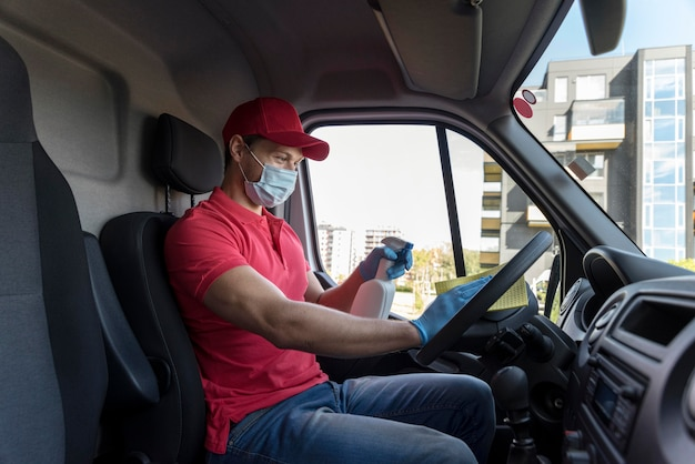 Vista lateral entregador com máscara de limpeza de carro Foto Premium