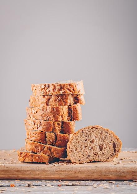 Vista lateral fatiada de pão na tábua na mesa de madeira e superfície cinza Foto gratuita