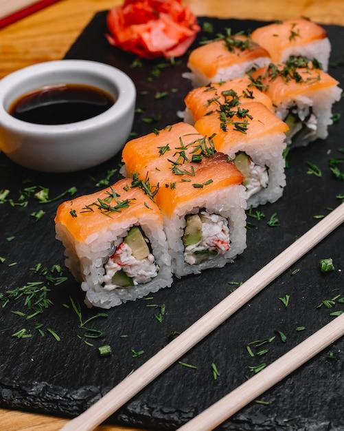 Vista lateral filadélfia roll salmão com carne de caranguejo abacate pepino endro gengibre e molho de soja em uma bandeja Foto gratuita