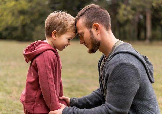 Vista lateral filho e filha ao ar livre Foto gratuita