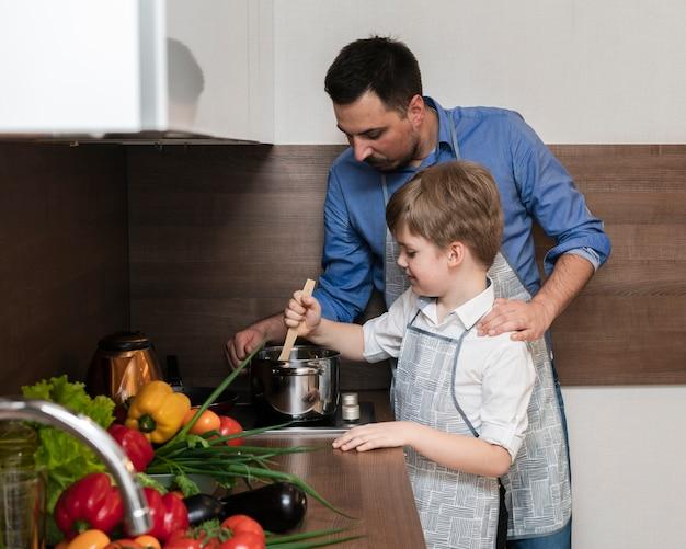Vista lateral filho e pai cozinhando juntos Foto gratuita