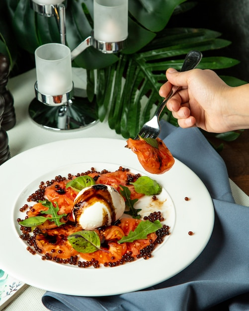 Vista lateral homem comendo salada de capricho com rúcula e caviar Foto gratuita