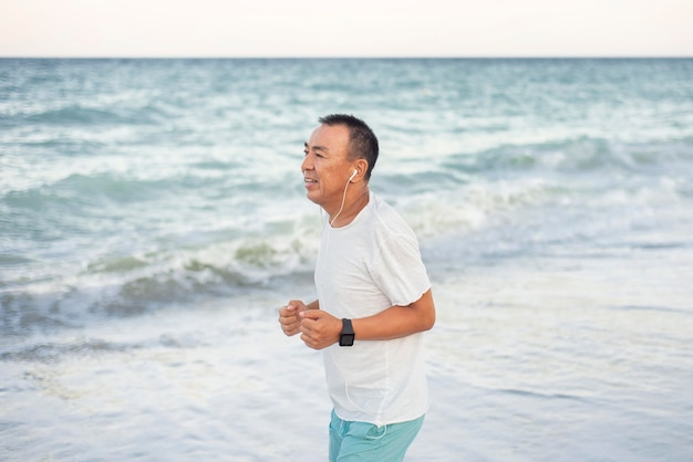Vista lateral homem correndo na praia Foto gratuita