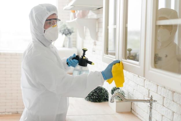 Vista lateral homem desinfecção de cozinha Foto Premium