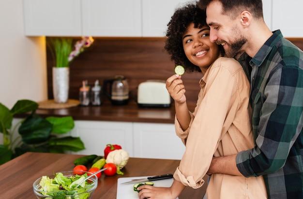 Vista lateral homem e mulher cozinhando juntos Foto gratuita