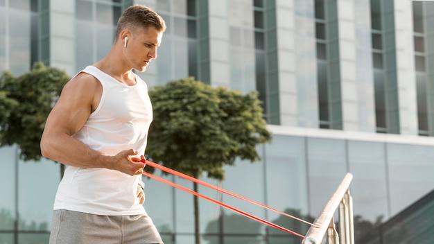 Vista lateral homem exercitando com uma faixa vermelha de alongamento Foto gratuita