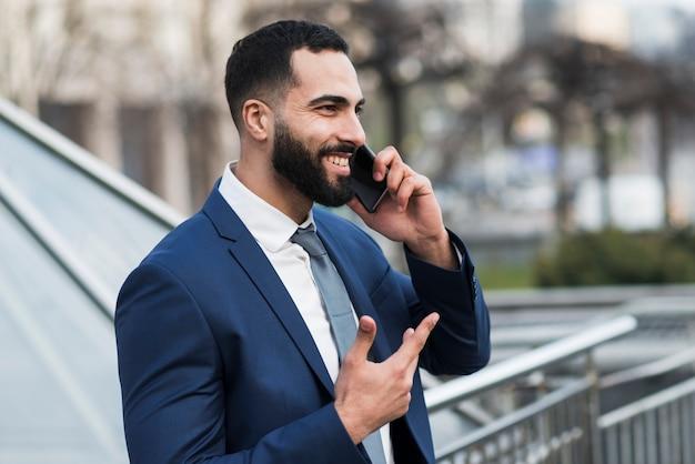 Vista lateral homem falando por telefone Foto gratuita