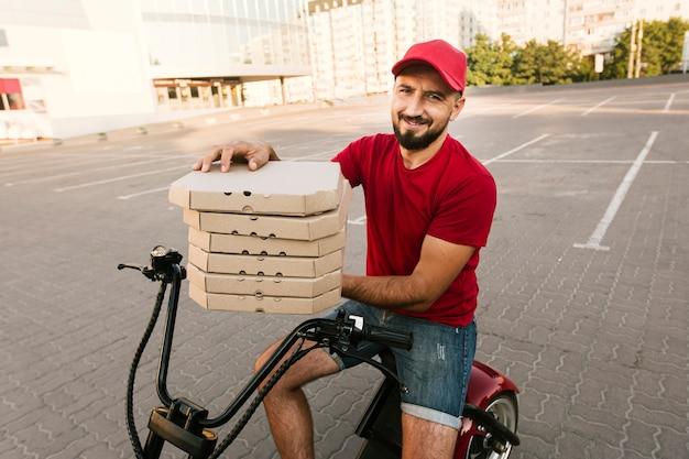 Vista lateral homem na moto segurando caixas de pizza Foto gratuita
