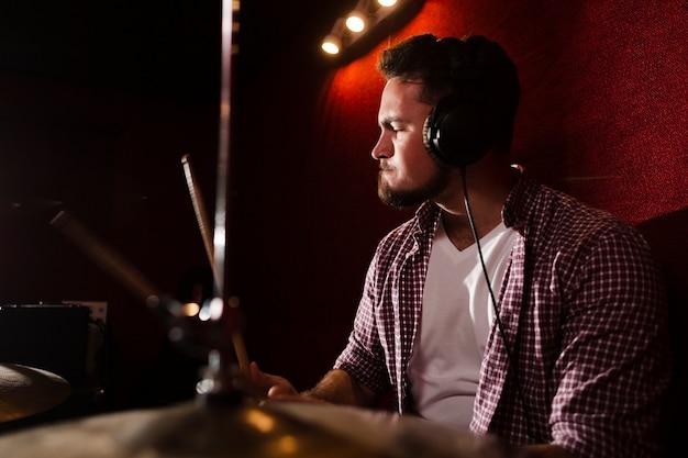 Vista lateral homem tocando bateria e usando fones de ouvido Foto gratuita