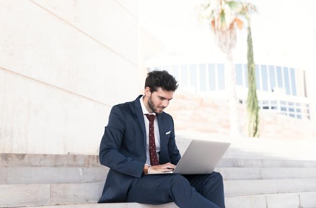 Vista lateral homem trabalhando sentado na escada Foto gratuita