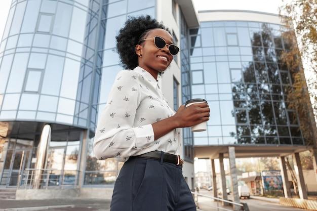Vista lateral jovem fêmea com café ao ar livre Foto gratuita