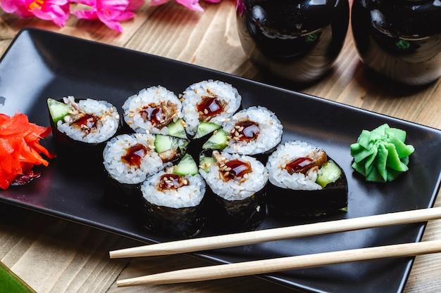 Vista lateral kappa maki com peixe frito pepino molho teriyaki wasabi e gengibre em uma placa Foto gratuita