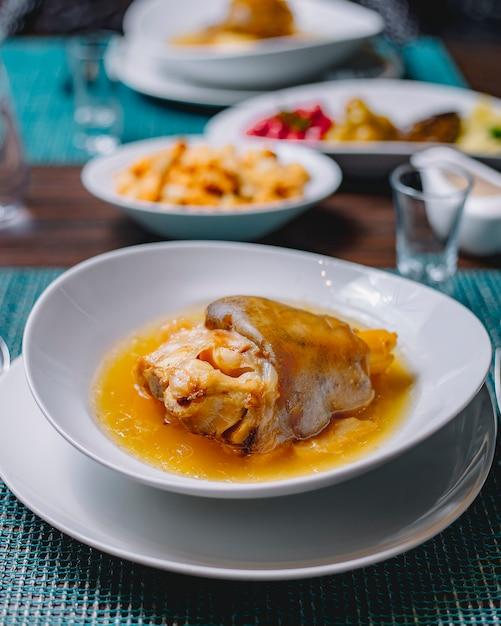 Vista lateral khash com pepino em conserva cereja berinjela ameixa cereja vinagre de alho e pão rusk em cima da mesa Foto gratuita