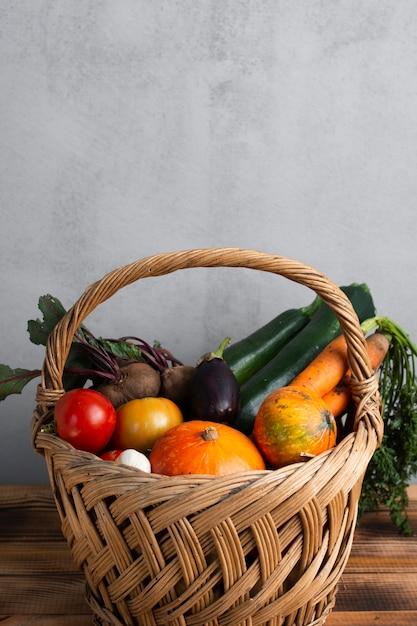 Vista lateral linda cesta cheia de legumes Foto gratuita
