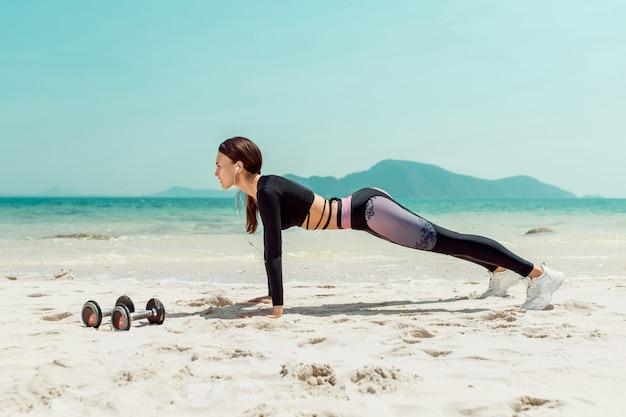 Vista lateral linda mulher desportiva na praia de posição de prancha. esporte . phuket. tailândia Foto Premium