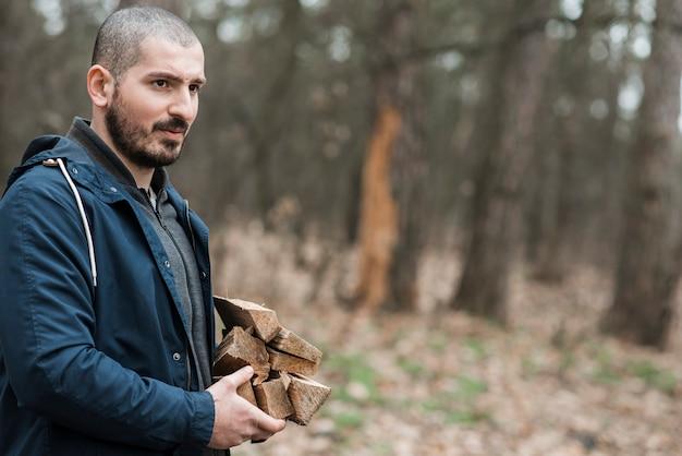 Vista lateral macho carregando madeira Foto gratuita