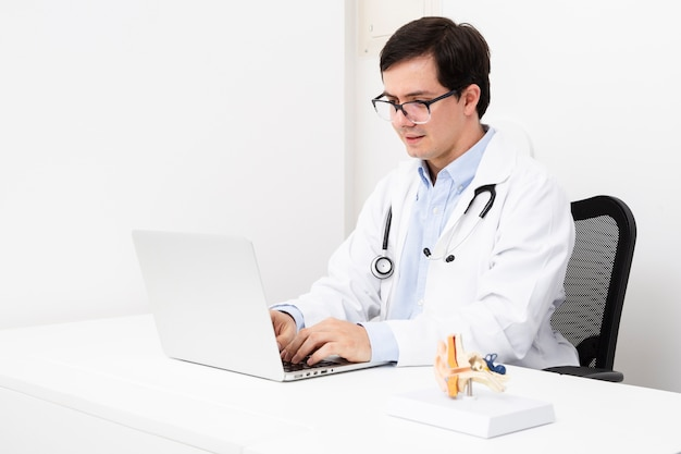 Vista lateral médico trabalhando no laptop Foto gratuita
