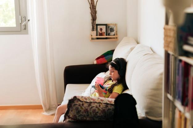 Vista lateral menina sentada no sofá com suco Foto gratuita