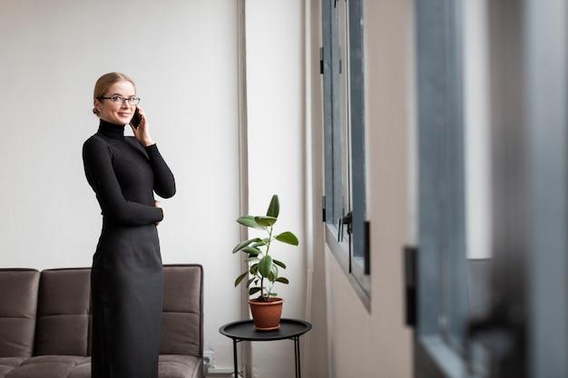 Vista lateral moderna fêmea falando por telefone Foto gratuita