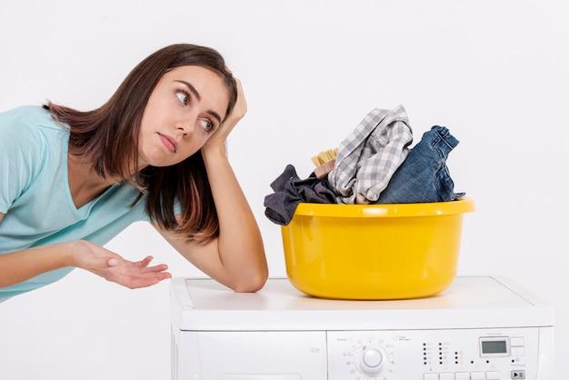 Vista lateral mulher entediada perto de cesto de roupa suja Foto gratuita