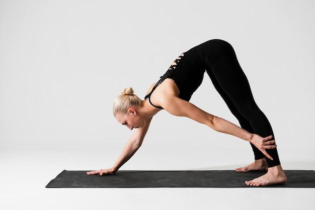 Vista lateral mulher exercitando na esteira Foto gratuita