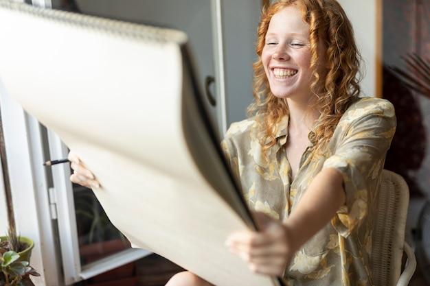 Vista lateral mulher feliz olhando o caderno Foto gratuita